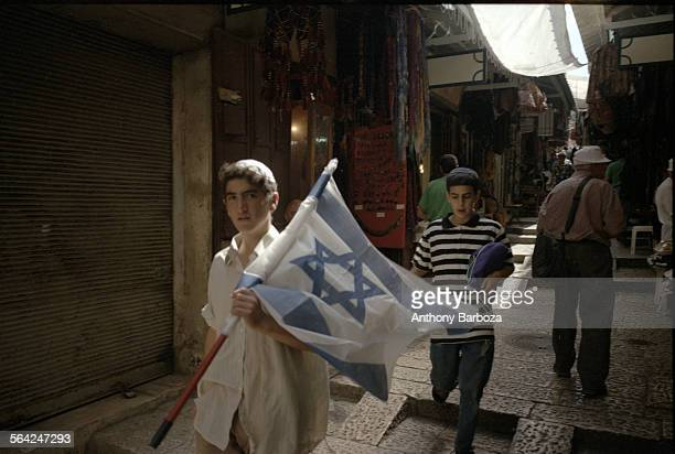 View of two boys one of who carries an Israeli flag as they walk along an unidentified street Old Jerusalem Israel 1980s