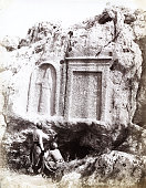 View of two men as they read carved writings on a stone face in a rock wall in the Middle East circa 1881