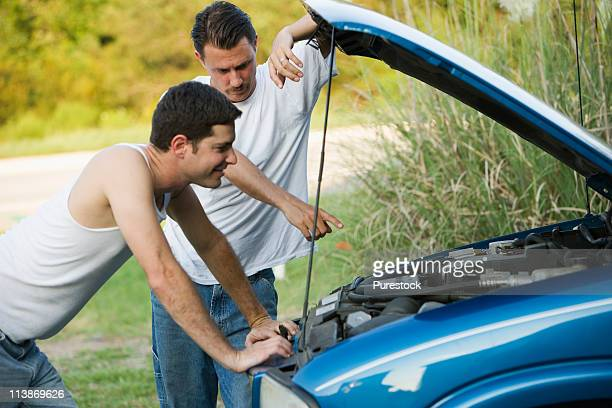 View of two men inspecting a car engine