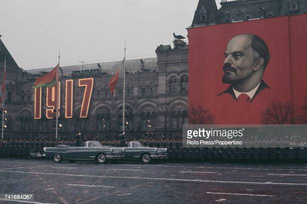 View of two open top ZIL111 limousines carrying Soviet Red Army generals driving past a line of Soviet troops during the annual November parade in...