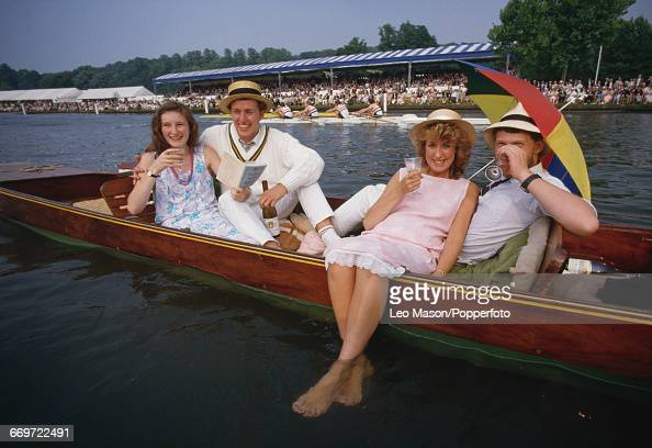 View of two spectating couples enjoying drinks whilst lying together in a punt on the River Thames at Henley during a rowing event at the Henley...