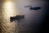 View of two unidentified merchant cargo ships from a convoy as they are escorted by a KClass patrol blimp mid 1940s