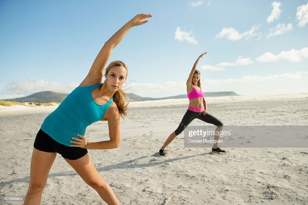 View of two young adult women, stretching arms : Foto de stock