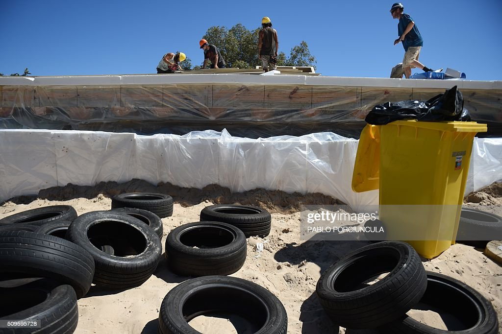 View of tyres to build walls during the construction of an auto-sustainable elementary school in Jaureguiberry -80 km east of Montevideo, Uruguay- on February 11, 2016. US architect Michael Reynolds, founder of Earthship Academy, gives training to 100 students from 30 countries (most of them architects) in Earthship design principles, construction methods and philosophy, to build the first school of this kind in the world. AFP PHOTO / PABLO PORCIUNCULA / AFP / PABLO PORCIUNCULA