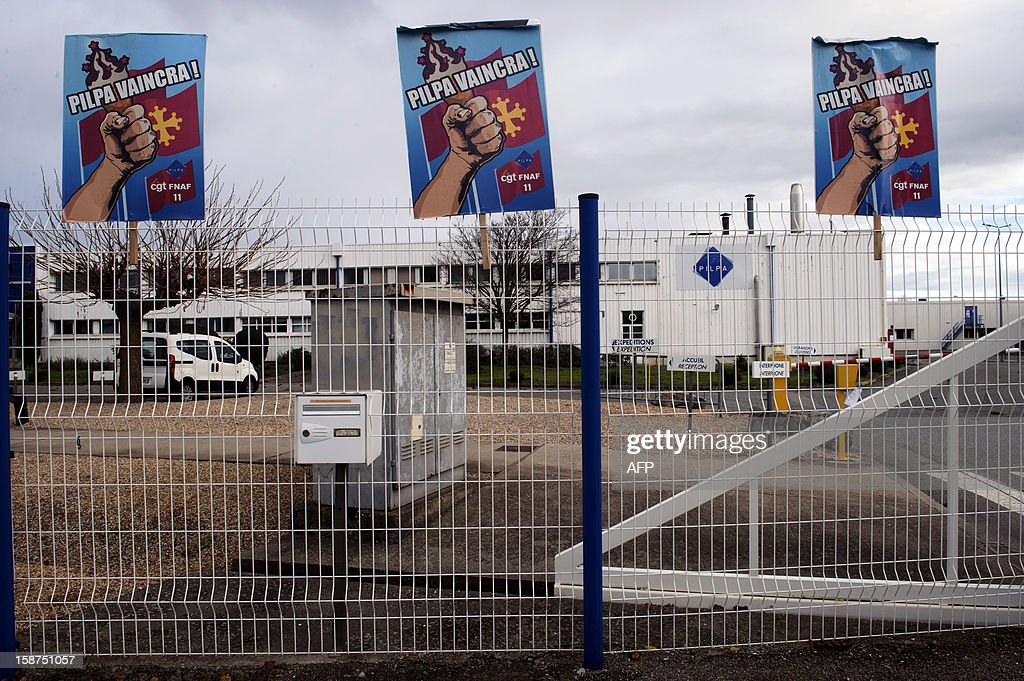 A view of union posters hanging on the fence surrounding the Pilpa ice cream factory in Carcassonne, southern France, as workers take part in surveillance rounds to stop the new factory owner from taking or dismantling factory equipment and machines, on December 27, 2012. 112 workers face the threat of being layed-off since July 2012 when the factory's owner sold the site to the R&R ice cream company and have struggled to keep the site and its jobs ever since. As the workers await court rulings pertaining to the factory site and its future, workers say they are being vigilant and have instituted rounds and a night guard to make sure R&R does not leave with the machines and equipment, thereby making it impossible for workers to consider continuing production at the site. AFP PHOTO / REMY GABALDA