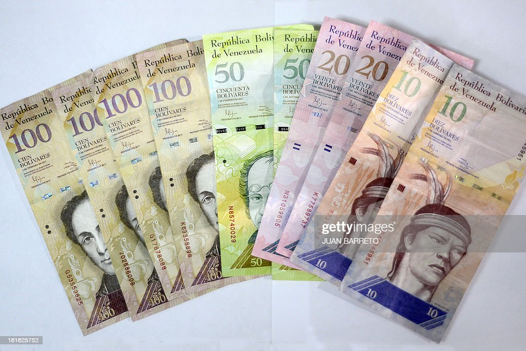 View of Venezuelan Bolivar notes in Caracas, on February 13, 2013. Venezuelans swamped stores on Tuesday to snap up everything from washing machines to plane tickets in a last-minute wave of panic-buying ahead of a 32 percent currency devaluation. AFP PHOTO/JUAN BARRETO