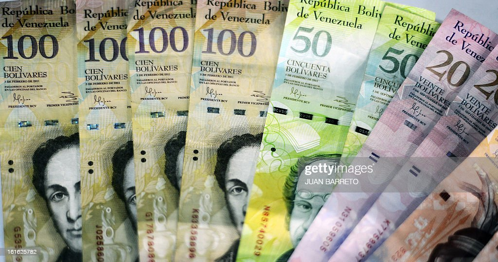 View of Venezuelan Bolivar notes in Caracas, on February 13, 2013. Venezuelans swamped stores on Tuesday to snap up everything from washing machines to plane tickets in a last-minute wave of panic-buying ahead of a 32 percent currency devaluation. AFP PHOTO