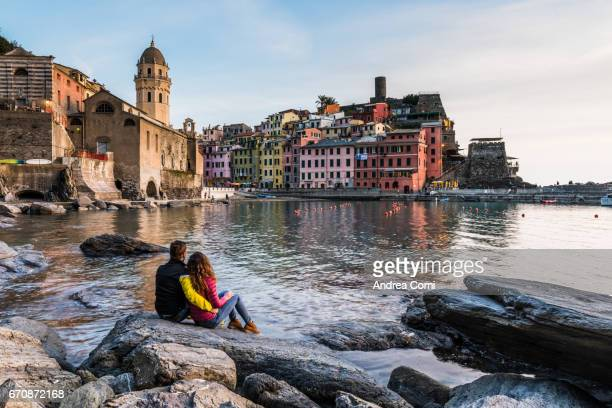 View of Vernazza from the bay. A couple is looking at the village. Cinque Terre, La Spezia, Liguria
