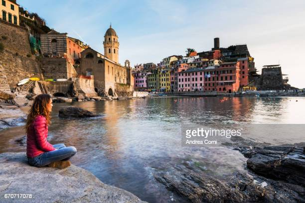 View of Vernazza from the bay. A girl is looking at the village. Cinque Terre, La Spezia, Liguria