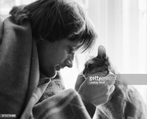 View of Viggo Mortensen a blanket wrapped about his shoulders as he holds the face of and looks into the eyes of Remy an Abyssinnian cat during a...