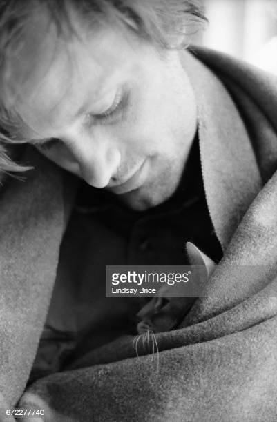 View of Viggo Mortensen a blanket wrapped about his shoulders as he holds Remy an Abyssinnian cat inside the blanket and close to his chest during a...