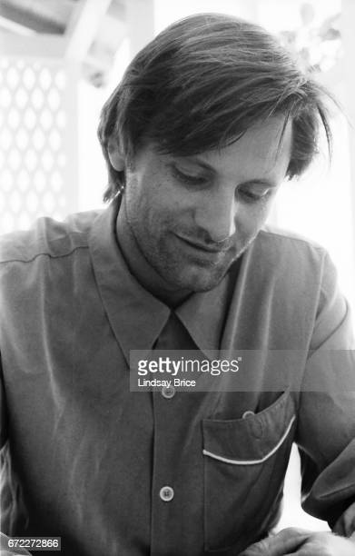 View of Viggo Mortensen as he sits on a porch latticework behind him wearing a Westernstyle buttondown shirt with white piping on the breast pocket...
