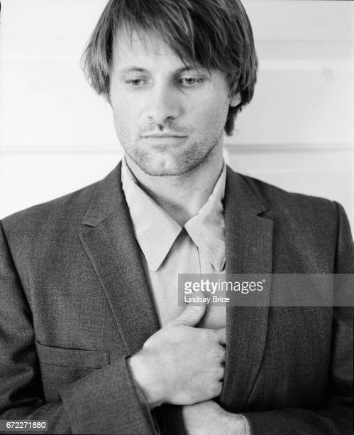 View of Viggo Mortensen as he stands wearing a buttondown shirt and sport coat he tucks his hands inside his coat lapels his right hand above his...