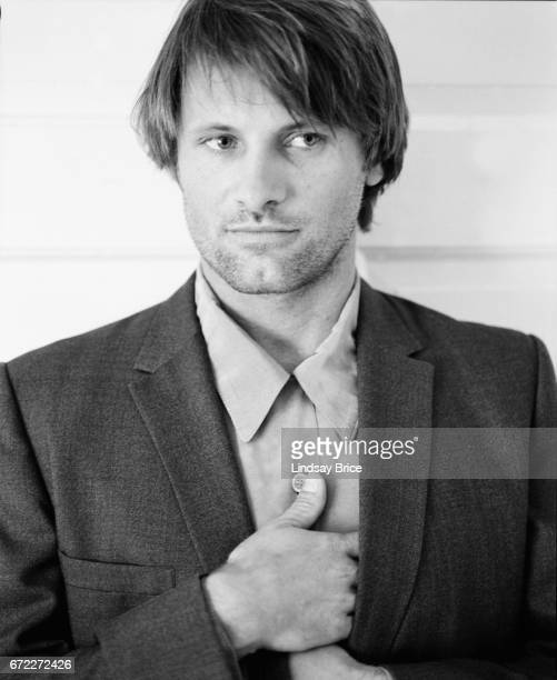 View of Viggo Mortensen standing wearing a buttondown shirt and sport coat he tucks his hands inside his coat lapels his right hand above his left...