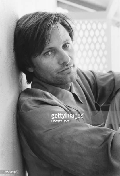 View of Viggo Mortensen wearing a Westernstyle buttondown shirt with piping on the breast pocket as he sits on a porch and leans against an exterior...