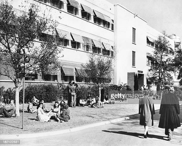 View of Walt Disney Studio employees as they relax on the lawn during their lunch hour Burbank California 1946