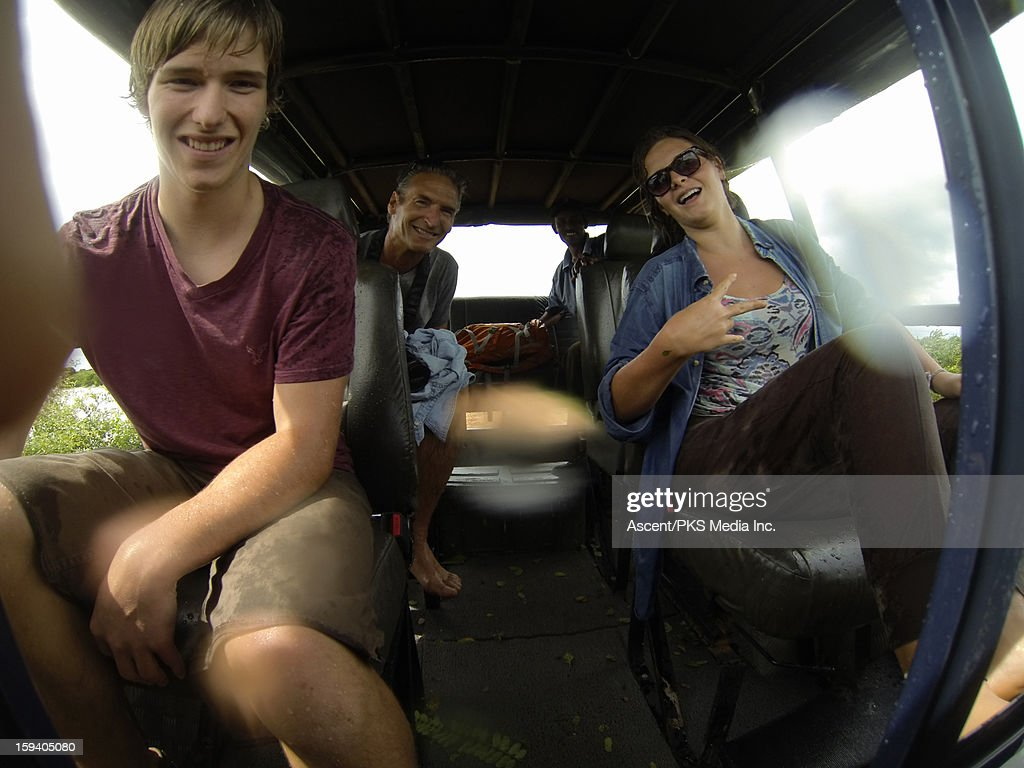 View of wet travellers in rear of safari jeep : Stock Photo