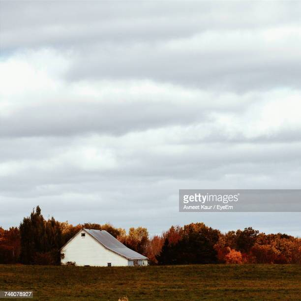 View Of White Barn On Field In Autumn With Overcast Sky