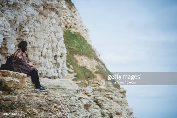 View Of Woman Sitting On Rock Face