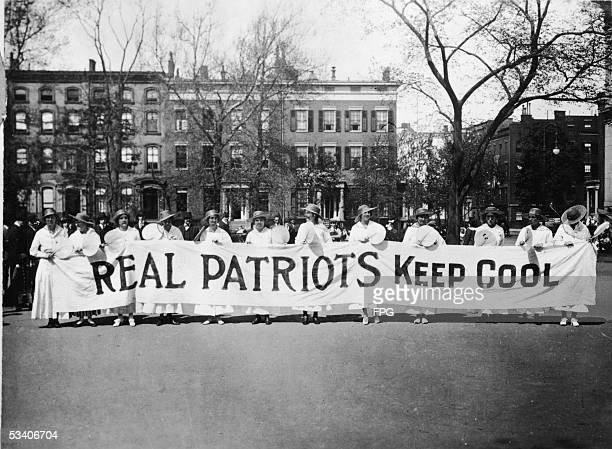 View of women from the Woman's Peace Party as they stand and hold a banner which reads 'Real Patriots Keep Cool' to demonstate against US involvment...