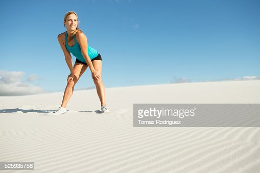 View of, young adult woman standing on sand in sports clothing : Stock Photo