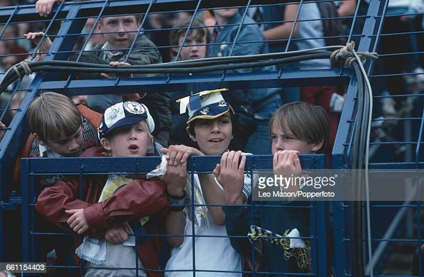 View of young boys football fans and supporters of Tottenham Hotspur holding on to the bars as they poke their heads through a gap in a metal crowd...