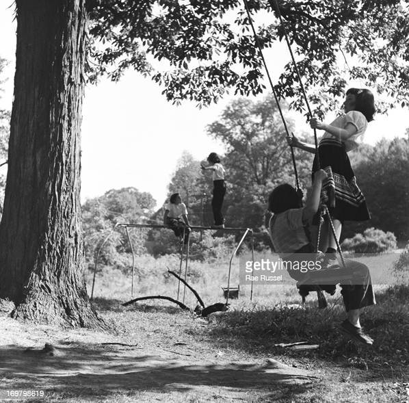 View of young girls sharing a tree swing at the Henry Street Settlement Summer camp New York New York 1948 Other girls are visible playing on a...