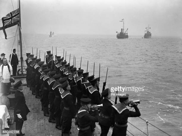 A view on board the 'Adamant' showing the crew sounding the Last Post and in the distance the 'Todworth' and the 'Moorside' the lifting lighter The...