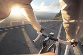 View on road through cyclists hands, sunrise