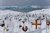 View on the icebergs in the Disko Bay from the cemetary of the town of Ilulissat Though the disappearing ice cap could lead to higher sea levels all...