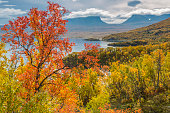 View over Abisko with Lapporten from Björkliden, at autumn season with yellow and red and orange trees and clouds hanging oveer the mountains, Abisko, Kiruna, Swedish Lapland, Sweden