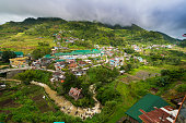 View over the village of Banaue and the mountains. Hanging bridge across the river.