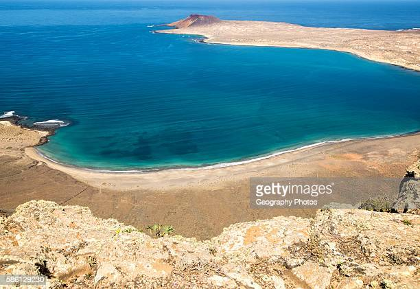 View over El Rio channel to the southern tip of Graciosa Island with sandy beach on Lanzarote in foreground Canary Islands Spain