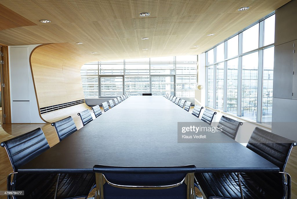 View over huge table in designed meeting room : Stock Photo