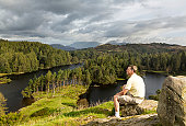 Senior hiker looks over Tarn Hows in English Lake District
