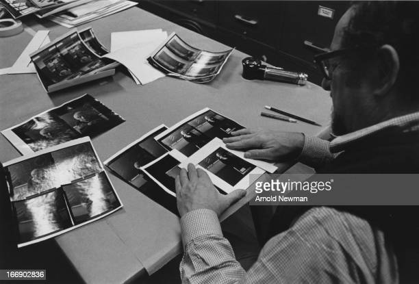 View over the shoulder of American photographer Arnold Newman as he crops contact sheets of British scientist Francis Crick 1979