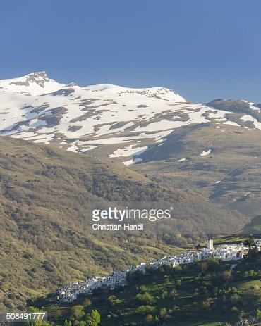 View over the town of Pampaneira towards the snow-capped Sierra Nevada Mountains, Pampaneira, Andalucia, Spain