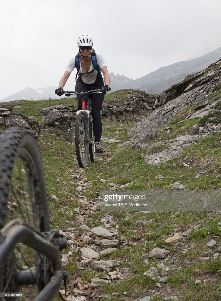 View past bike tire to woman descending mtn slope : Stock Photo