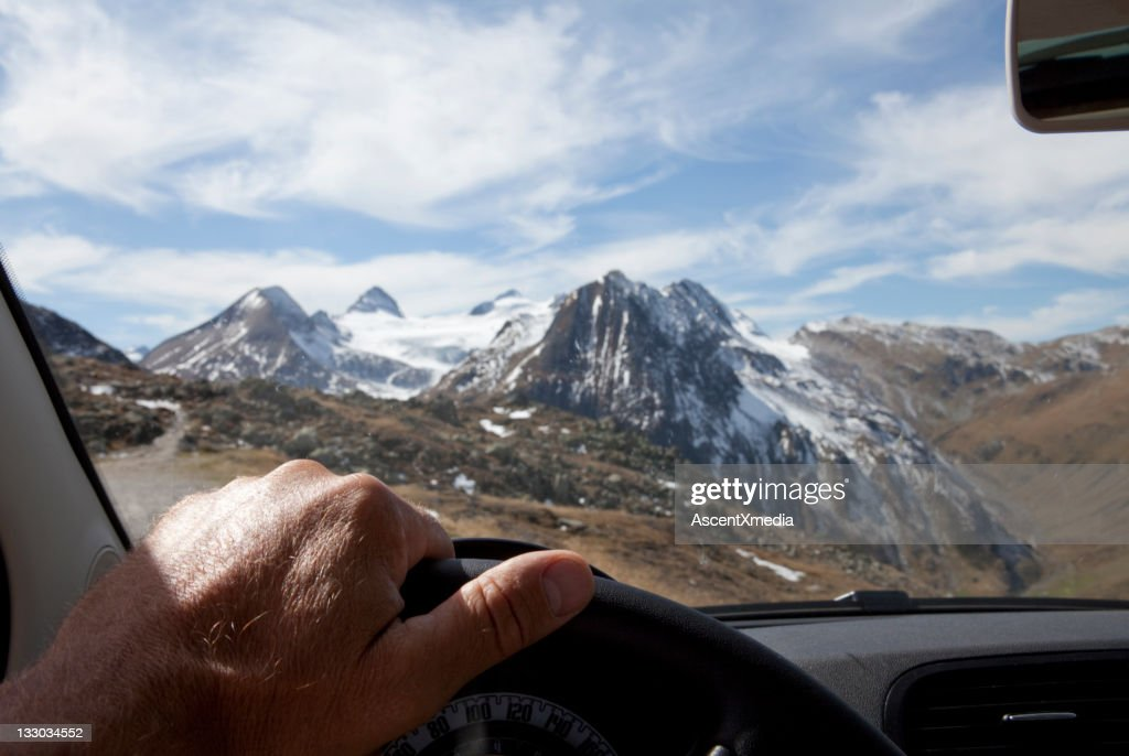 View past driver's hand to snow capped mountains : Stock Photo