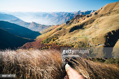 View past legs of trail runner to mountain ranges