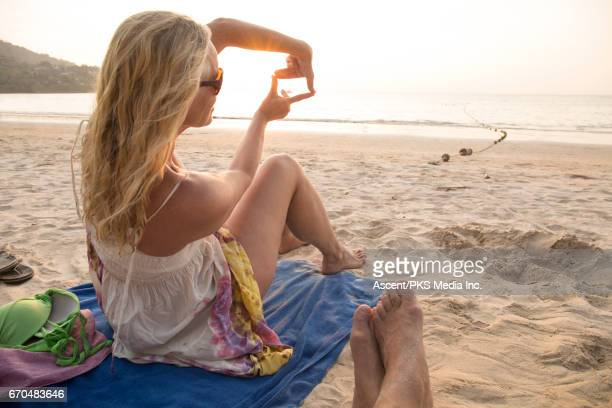 View past man's feet to woman framing sunrise over beach