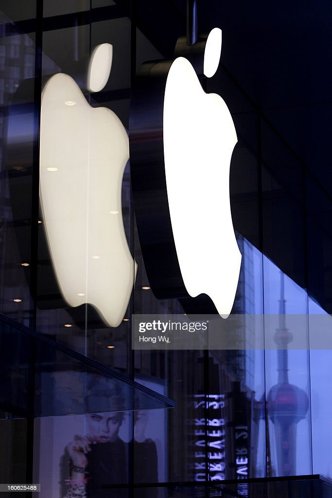 A view shows inverted image of the Oriental Pearl TV Tower near by a big Apple store logo in Nanjing Road Walking Street on February 3, 2013 in Shanghai, China.