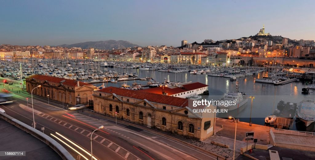 View taken at sunset on January 03, 2013 of the 'Vieux-Port' (Old Harbour) in the French southern city of Marseille, one week ahead of the 2013 'Marseille-Provence European Capital of Culture' event. In the background, at center, is seen the Notre-Dame de la Garde basilica. AFP PHOTO/GERARD JULIEN