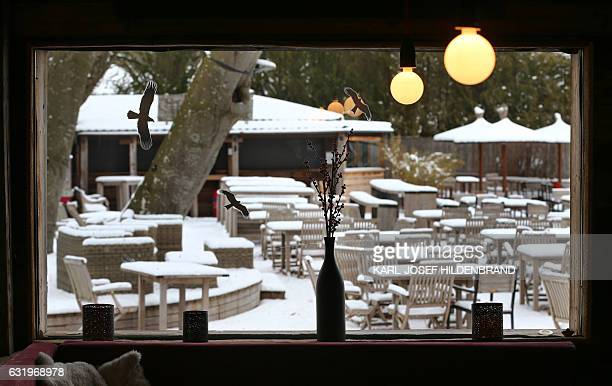 View taken from a restaurant's window shows tables and chairs of a beer garden covered in snow on January 18 2017 near Inning am Ammersee southern...