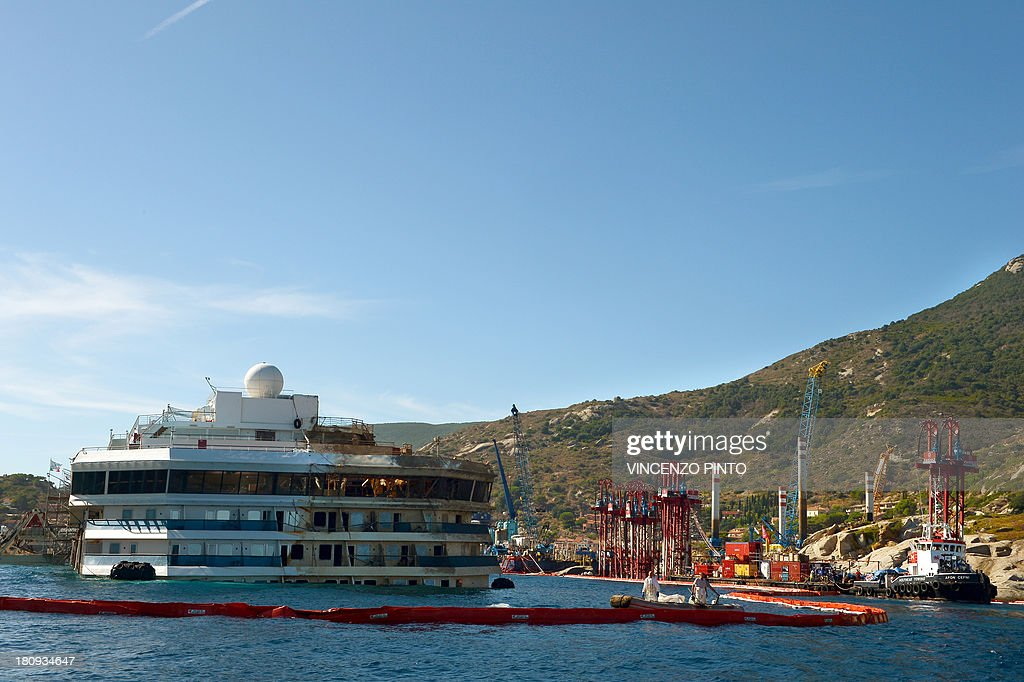 A view taken from the Coast Guard ship on September 18, 2013, shows the wreck of Italy's Costa Concordia cruise ship after emerging from water, near the harbour of Giglio Porto. Salvage operators in Italy lifted the Costa Concordia cruise ship upright from its watery grave off the island of Giglio in the biggest ever project of its kind. The ship was upright for the first time since the January 13, 2012 tragedy, and led to applause and cheers in the port, in a dramatic climax to the massive salvage operation. Local residents and survivors spoke of an eerie feeling as the ship rose, saying the sight reminded them of the tragedy that claimed 32 lives..