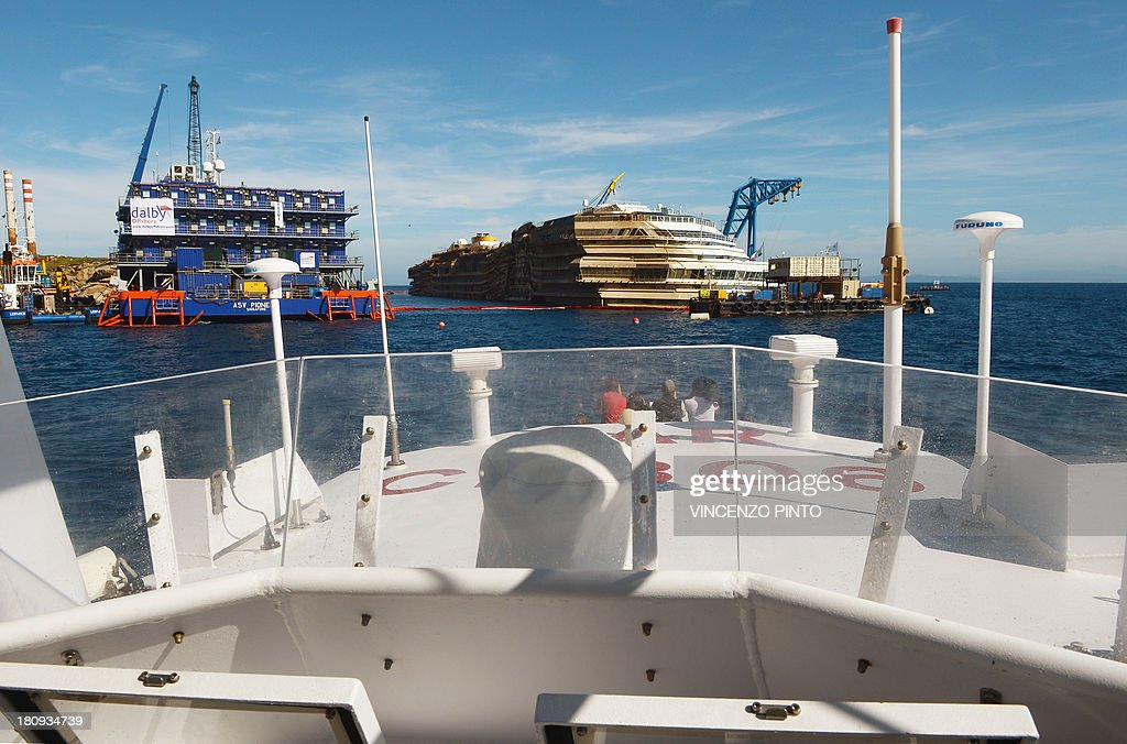 A view taken from the Coast Guard ship on September 18, 2013, shows the wreck of Italy's Costa Concordia cruise ship after emerging from water, near the harbour of Giglio Porto. Salvage operators in Italy lifted the Costa Concordia cruise ship upright from its watery grave off the island of Giglio in the biggest ever project of its kind. The ship was upright for the first time since the January 13, 2012 tragedy, and led to applause and cheers in the port, in a dramatic climax to the massive salvage operation. Local residents and survivors spoke of an eerie feeling as the ship rose, saying the sight reminded them of the tragedy that claimed 32 lives.