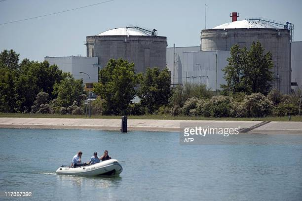 View taken of the nuclear powerplant of Fessenheim eastern France as French policemen patrol on Le Grand Canal d'Alsace during a demonstration of...