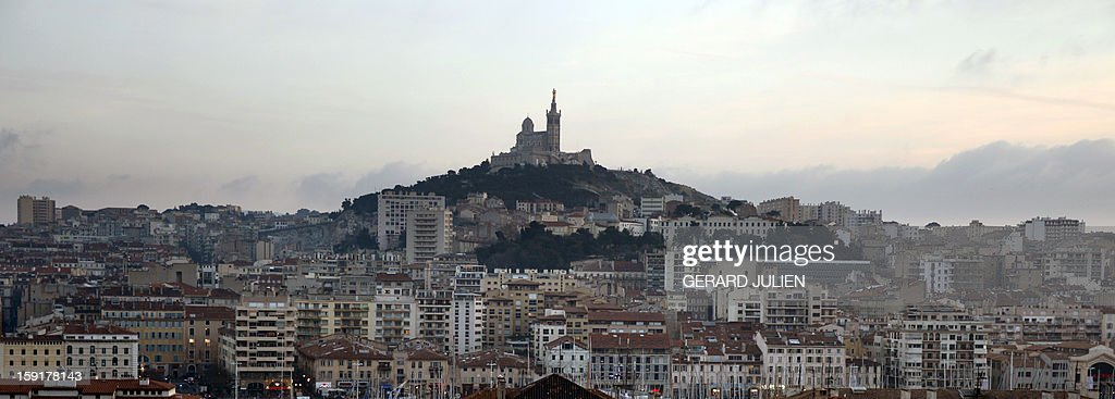 View taken on January 9, 2013 of the 'Vieux-Port' (Old Harbour) and the Notre-Dame-de-la Garde basilica in the French southern city of Marseille, two days ahead of the 2013 'Marseille-Provence European Capital of Culture' event. AFP PHOTO/GERARD JULIEN