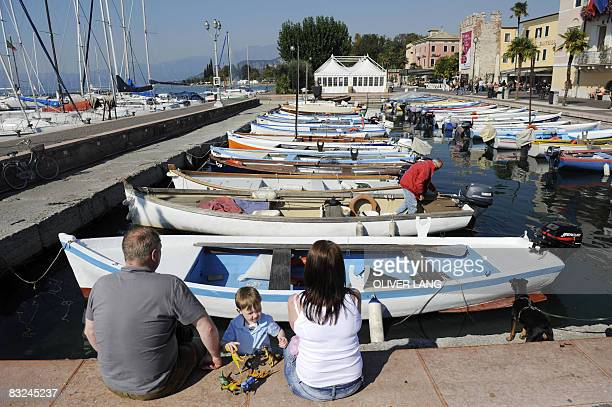View taken on Oktober 8 2008 shows a family sitting near a small harbour at the Lake Garda in Bardolino northern Italy The Garda Lake is the largest...
