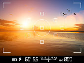 View through the viewfinder of a DSLR camera of photographer and traveler taking a picture of a beautiful sunset over the sea, with birds flying away.  Display shows data about exposure, shutter speed